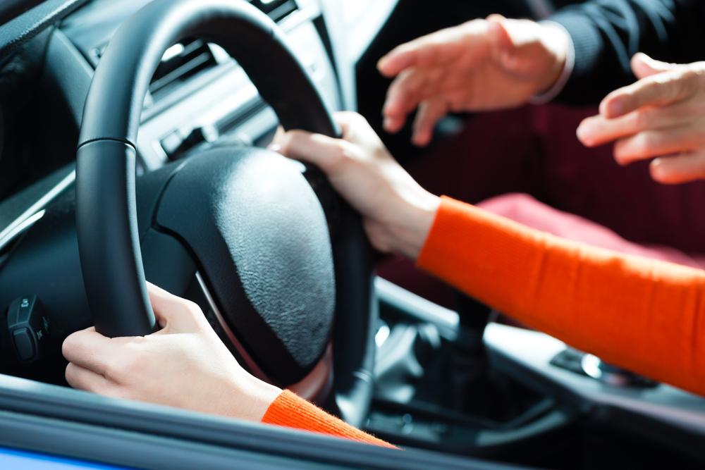Focus sur les mains d'une jeune conductrice au volant d'une voiture accompagnée de son moniteur